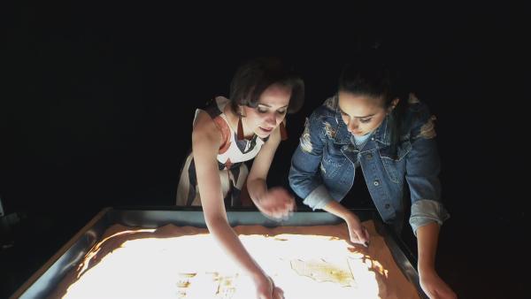 Jess probiert das Malen mit Sand aus und bekommt von Künsterlerin Irina (li.) einen Kunstunterricht der besonderen Art. | Rechte: KiKA
