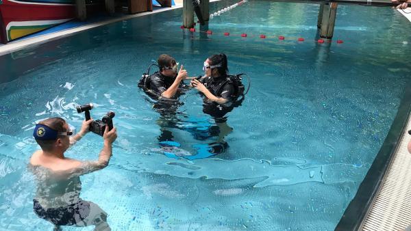 Tobi zeigt Jess, mit welchen Handzeichen sich Taucher unter Wasser verständigen. | Rechte: KiKA/Stefanie Jung