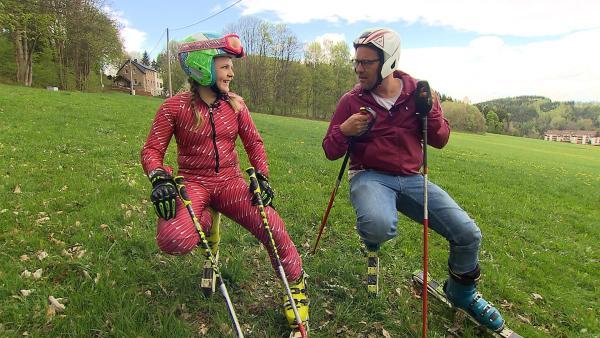 Johanna nimmt Ben mit auf die Graspiste und zeigt ihm, wie man auch im Sommer Ski fahren kann. | Rechte: KiKA