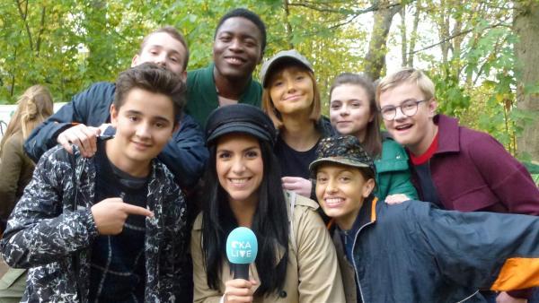 """Jess ist unterwegs mit dem """"Schloss Einstein""""-Team. Diesmal treffen sich viele Darsteller für eine große Szene im Wald.   Rechte: KiKA/Andrea Thoben"""