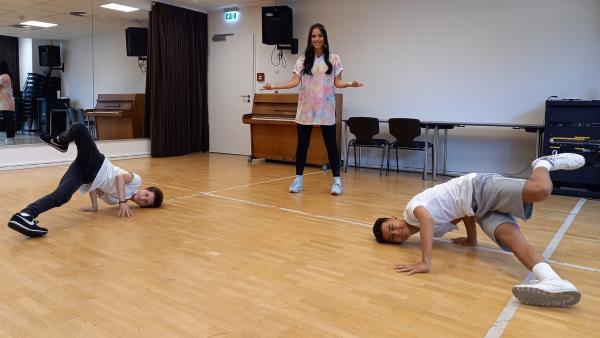 Jess mit Philip und Anton. Sie nehmen Jess mit in ihre Welt – also mit auf den Boden. Drehen auf dem Kopf und das ohne Arme? | Rechte: KiKA/Anna-Maria Leistner