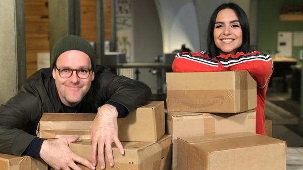 Jess und Ben sind im Unboxing-Fieber: Zwei Tage lang dürfen sie lauter Kartons mit unbekanntem Inhalt auspacken. In manchen verbergen sich wahre Schätze, die ihnen sofort ans Herz wachsen oder den Bauch lecker füllen | Rechte: KiKA/Rozhyar Zolfaghari