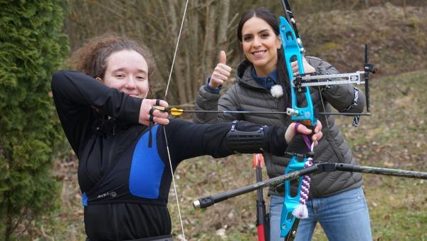 Jess schaut Nevena beim Bogenschießen über die Schulter. | Rechte: KiKA/Franziska Gruber