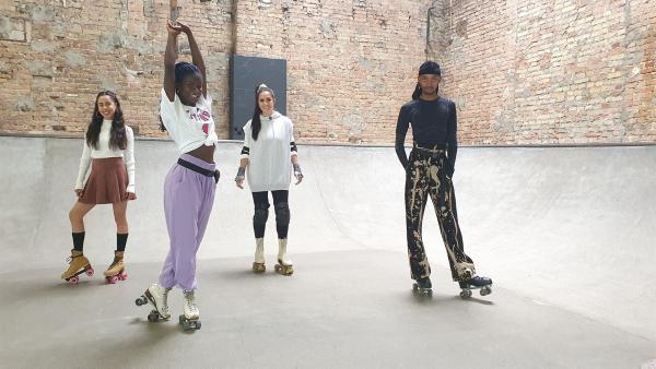 Oumi (2.v.l.) lädt Jess zu einem Workshop ein und bringt ihr ein paar coole Moves auf Rollerskates bei. | Rechte: KiKA/Stefanie Jung