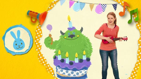Anni sendet Glückwünsche zum Geburtstag und singt ein Geburtstagslied. Kikaninchen hört aufmerksam zu.  | Rechte: KiKA