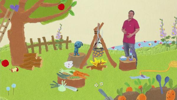 KIkaninchen und Christian kochen auf einer Wiese in einem Kessel über einem Lagerfeuer eine leckere Gemüsesuppe.  | Rechte: KiKA
