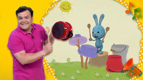 Christian lacht udn schlägt mit einem Holzlöffel auf einen roten Kochtopf, den er in der Hand hält. Kikaninchen trommelt mit zwei Holzlöffeln auf ein Schlagzeug aus Töpfen. | Rechte: KiKA