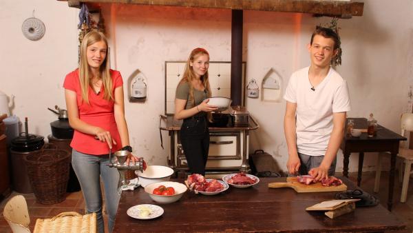 Regina, Celine und Paul müssen mit einem Fleischwolf rohes Fleisch für die Burgerpattys zubereiten.   Rechte: ZDF/Oliver Landgraf