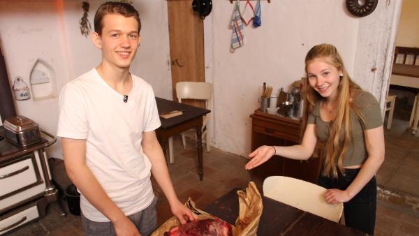 Team Vergangenheit bereitet Burgerpattys auf altmodische Weise zu. Paul und Celine begutachten das rohe Fleisch, dass durch den Fleischwolf gedreht werden muss.   Rechte: ZDF/Oliver Landgraf