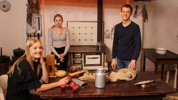 (V.l.) Regina, Celine und Paul möchten Bircher Müsli zubereiten. Die Haferkörner müssen geflockt werden und für die Milch muss eine Kuh gemolken werden! | Rechte: ZDF/Oliver Landgraf
