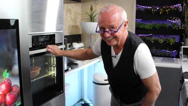 Ein älterer Herr, Wolfgang aus dem Team Zukunft, steht lächelnd vor einem Ofen, in dem ein Kuchen backt. | Rechte: ZDF/ Endemol Shine