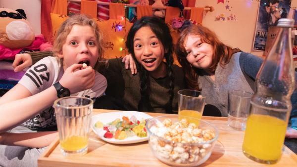 Ole, Nhung und Elisabeth haben sich zu einem gemütlichen Filmabend getroffen und naschen Snacks. | Rechte: rbb/Albrecht Elstermann