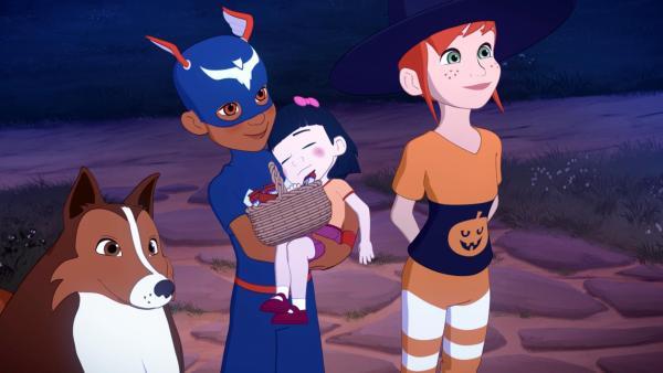 Lassie, Zoé und Harvey sind in Halloweenkostümen verkleidet. Harvey trägt ein kleines Mädchen im Arm, das schläft. | Rechte: Superprod, ZDF, ZDFE
