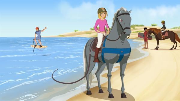 Samantha (Mi.) zieht Nico auf seinem Surfbrett (li.). | Rechte: hr/Télé Images