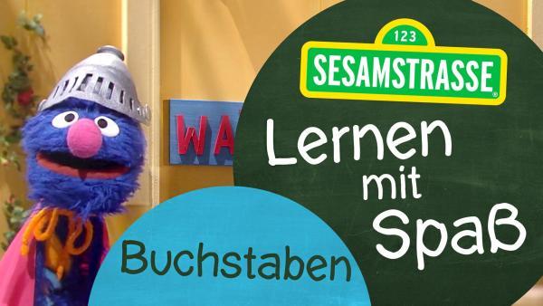 """Groby trägt einen Ritterhelm und steht neben einem Schild auf dem steht: """"Sesamstraße: Lernen mit Spaß - Buchstaben"""".   Rechte: NDR"""