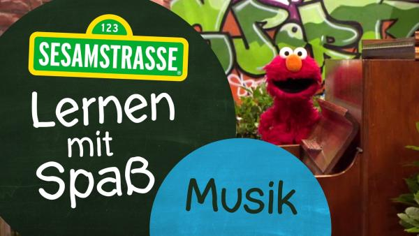 """Elmo steht vor einer Wand mit Graffiti und hinter einem braunen Klavier. Neben ihm steht ein Schild auf dem steht: """"Sesamstraße: Lernen mit Spaß - Musik"""".   Rechte: NDR"""