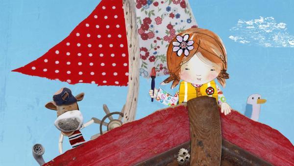 Lily freut sich, dass sie einen Pinsel am Strand gefunden hat.  | Rechte: KiKA/Sixteen South