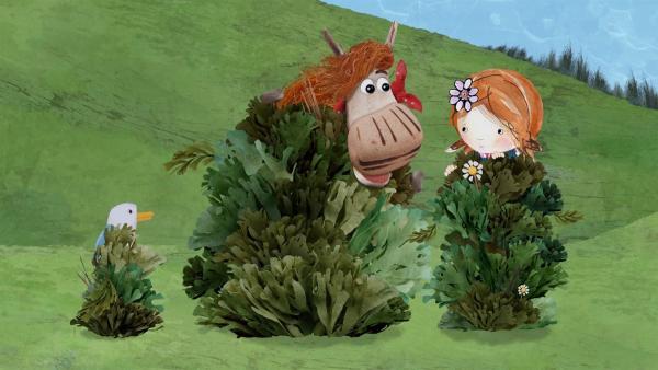 Lily, Barne und Pelle schleichen sich mit Tarnbüschen an das geflohene Schaf an. | Rechte: KiKA/Sixteen South