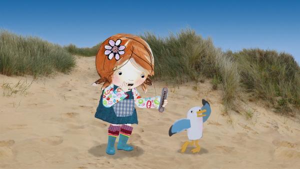 Lily überlegt, was man auf der Mundharmonika, die sie am Strand gefunden hat, alles spielen kann. | Rechte: KiKA/Sixteen South
