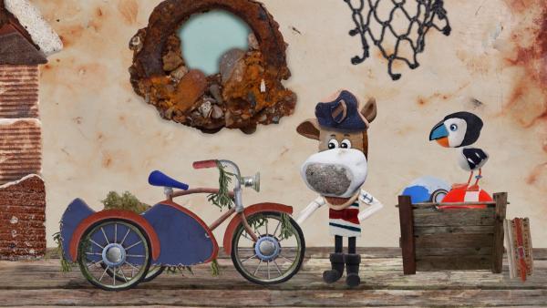 Salty zeigt Jette und Lily stolz sein Fahrrad mit Beifahrersitz, das Puffin am Morgen aus dem Hafenbecken geholt hat. | Rechte: KiKA/Sixteen South