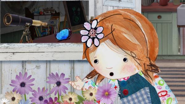 Lily entdeckt einen wunderschönen Schmetterling. Leider fliegt er weg, als sie ihn auf ihre Hand nehmen will. | Rechte: KiKA/Sixteen South