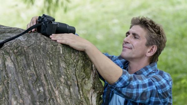 Fritz Fuchs (Guido Hammesfahr) auf Foto-Tour durch Bärstadt. Er stellt die Kamera auf, um ein Foto von sich und Keks an ihrem Lieblingsplatz im Park aufzunehmen. | Rechte: ZDF/Antje Dittmann