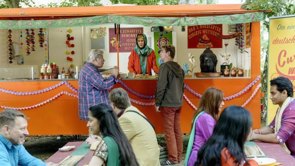 Am indischen Currywurst-Stand  von Indira (Beatrice Richter, hinten Mitte) treffen sich die beiden Streithähne Fritz Fuchs (hinten, r.) und Nachbar Paschulke (hinten, l.) fürs Schärfewettessen. | Rechte: ZDF/Antje Dittmann