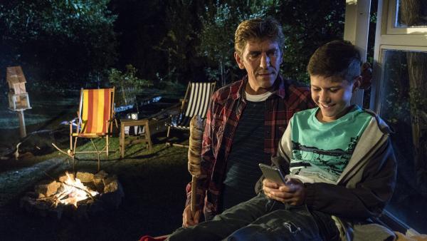 Selbst mit einem schönen Lagerfeuer kann Fritz Fuchs (Guido Hammesfahr, l.) Mattis (Noah Calvin, r.) nicht vom Smartphone weglocken. | Rechte: ZDF/Antje Dittmann