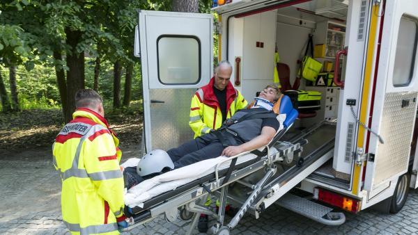 Fritz Fuchs (Guido Hammesfahr, liegend) hatte einen heftigen Fahrradunfall. Zum ersten Mal wird er mit einem Krankenwagen transportiert. Ein merkwürdiges Gefühl. | Rechte: ZDF/Ole Schwarz