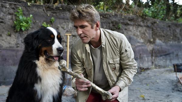 Hund Keks und Fritz Fuchs (Guido Hammesfahr) sitzen nebeneinander in der Baugrube und begutachtet einen alten Knochen. | Rechte: ZDF/Antje Dittmann