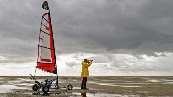 Mitten im Watt kann Fritz Fuchs (Guido Hammesfahr) nicht mit seinem Strandsegler losdüsen. Aber weit hinten entdeckt er eine Stelle, an der schon andere Sportler unterwegs sind. | Rechte: ZDF/Antje Dittmann