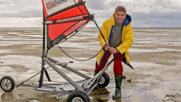 Der Strandsegler wird klar gemacht. Fritz Fuchs (Guido Hammesfahr) will dem stürmischen Tag trotzen. Eigentlich sollte er nur den Ordnungsamtmann zum Meer fahren, aber jetzt ist die Gelegenheit günstig, das Watt kennenzulernen. | Rechte: ZDF/Antje Dittmann