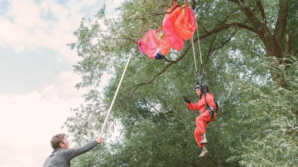 Irgendwie muss er doch die abgestürzte Rosi (Renate Serwotke) samt Fallschirm aus der Baumkrone bekommen. Fritz Fuchs (Guido Hammesfahr) gibt alles. | Rechte: KIKA/Bildredaktion
