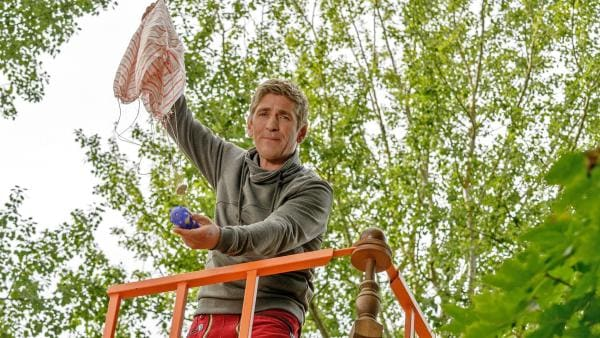 Start für den Test-Fallschirm. Fritz Fuchs (Guido Hammesfahr) versucht, etwas zu erfinden, an dem eine Kamera schweben kann. Er braucht es dringend, um den verschwundenen Herrn Kluthe in den Feldern zu finden. | Rechte: KiKA/Bildredaktion