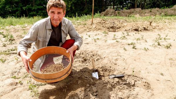 Fritz Fuchs (Guido Hammesfahr) sucht im Boden nach Lebewesen, doch irgendetwas stimmt nicht mit dem Erdreich. Müsste es hier nicht vor Kleintieren wimmeln? | Rechte: ZDF/Antje Dittmann