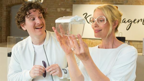Assistent Thorben (Dominik Weber) überreicht seiner Chefin Karla Lagerloef (Katja Weitzenboeck) ein kostbares Geschenk. | Rechte: ZDF/Zia Ziarno