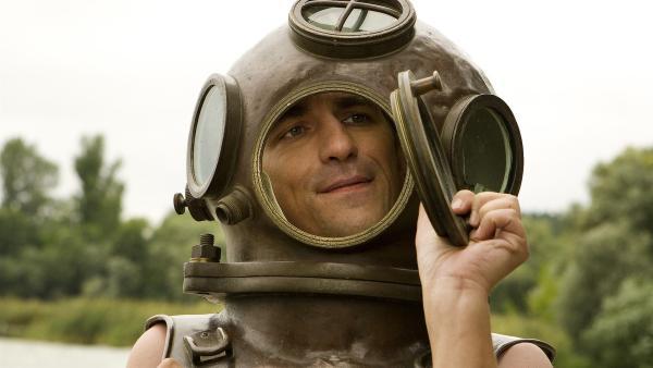 Fritz Fuchs (Guido Hammesfahr) hat im Bärstädter See einen alten Taucherhelm gefunden - und probiert ihn gleich mal an. | Rechte: ZDF/Antje Dittmann