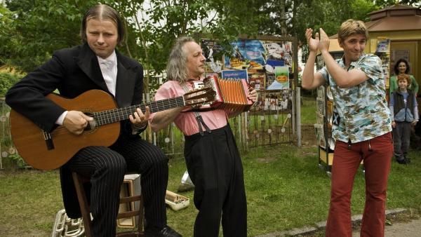 Die beiden Musikclowns Gogol (Christoph Schelb)und Mäx (Max-Albert Müller) legen mit Fritz Fuchs (Guido Hammesfahr) eine flotte Nummer am Büdchen hin. | Rechte: ZDF/Thomas Bergmann