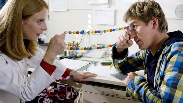 Die Orthoptistin (Julia Jäger) in der Sehschule zeigt Fritz Fuchs (Guido Hammesfahr) wie sie mit einfachen Dingen arbeitet. | Rechte: ZDF/Antje Dittmann