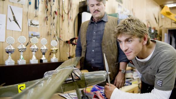 Fritz (Guido Hammesfahr) bestaunt die Modellflugzeuge von Modellflugexperte Henry Brettkamp (Christian Fischer). | Rechte: ZDF/Antje Dittmann