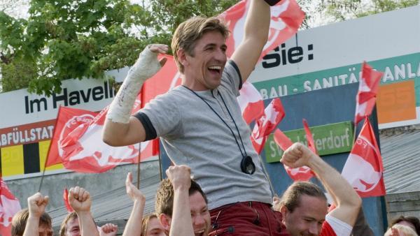Juchuh! Am Ende haben die Bärstädter doch noch das Pokalspiel gewonnen. Sie feiern ihren Trainer Fritz Fuchs (Guido Hammesfahr) | Rechte: ZDF/Antje Dittmann