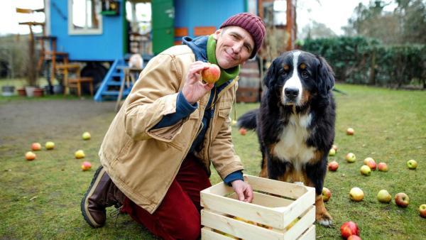 Fritz hockt mit Keks vor dem Bauwagen und hält einen Apfel in der Hand | Rechte: ZDF