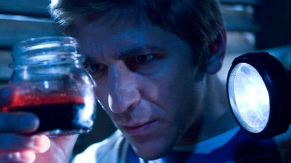 Fritz untersucht ein Glas in dem eine rote Flüssigkeit ist. | Rechte: ZDF