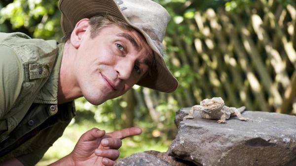 Fritz Fuchs mit Hut zeigt auf eine Echse, die auf einem Stein sitzt. | Rechte: ZDF