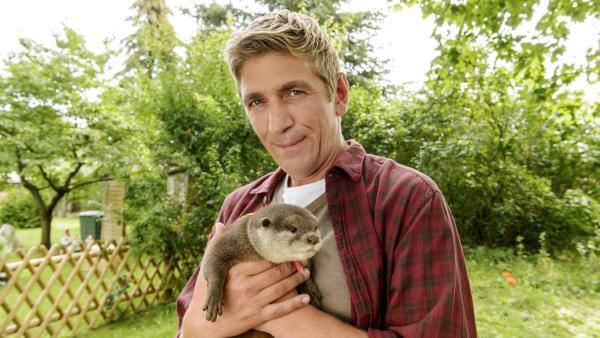 Fritz Fuchs steht im Garten und hält einen Fischotter in den Händen. | Rechte: ZDF