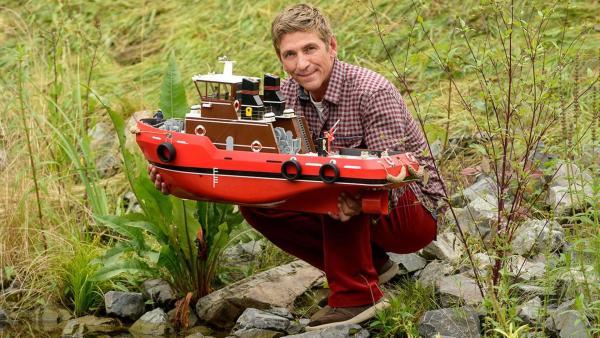 Fritz hockt am Flussufer mit dem Boot Heinz 1 in der Hand. | Rechte: ZDF
