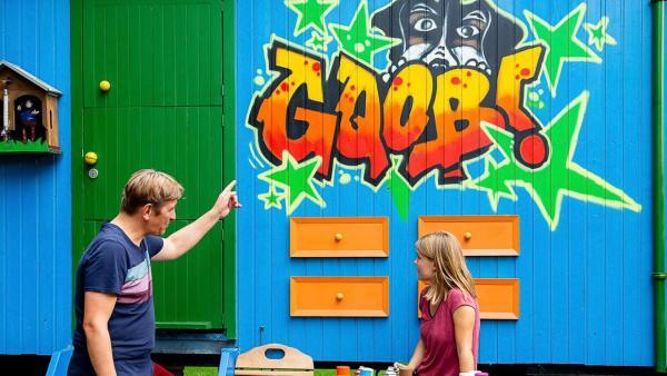 Fritz zeigt auf die Bauwagenwand, auf der ein Graffiti gesprüht wurde. Ein Mädchen steht davor.   Rechte: ZDF