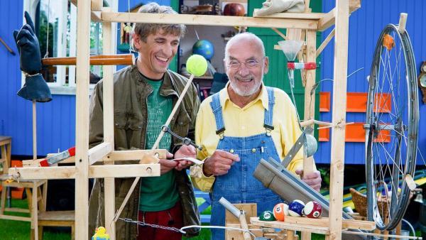 Fritz Fuchs und Peter Lustig stehen an einer Erfindung und lachen.   Rechte: ZDF