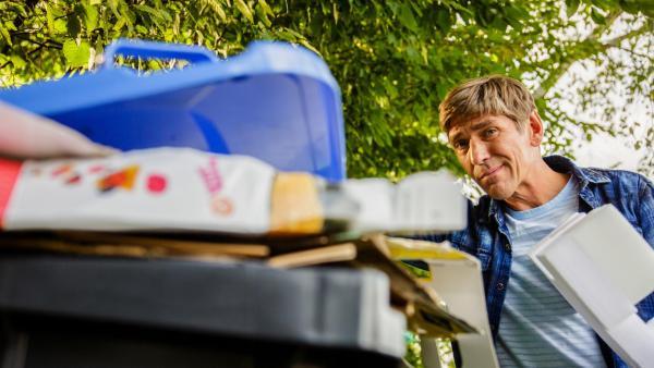 Fritz steht mit Müll beladen vor einer Mülltonne | Rechte: ZDF