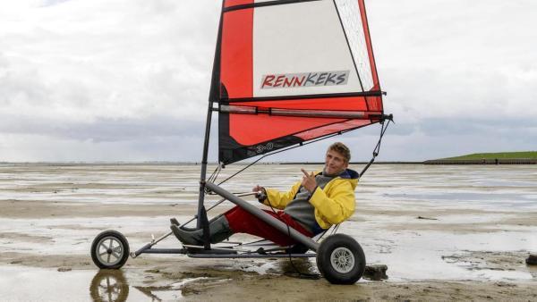 Fritz Fuchs sitzt in einem Strandsegler. Es ist Ebbe, das Meer hat sich zurückgezogen.   Rechte: ZDF